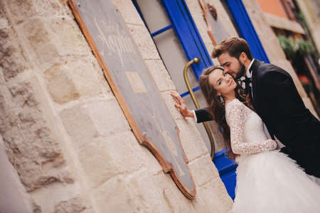 Happy newlywed couple hugging and kissing in old European town street, gorgeous bride in white wedding dress together with handsome groom. wedding day Foto de archivo