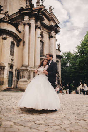 Happy newlywed couple hugging and kissing in old European town street, gorgeous bride in white wedding dress together with handsome groom. wedding day. Foto de archivo
