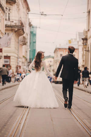 Happy newlyweds couple on a walk in old European town street, gorgeous bride in white wedding dress together with handsome groom. rear view.