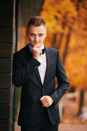 stylish young groom in a black suit in the autumn park on wedding day.