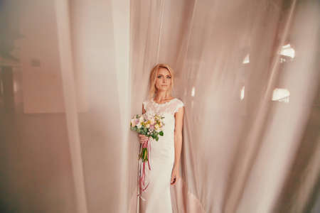 portrait of a beautiful young woman bride in a white dress with a bouquet of flowers in her hands on white background. wedding day.