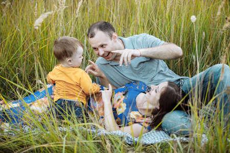 妈妈,爸爸和小儿子坐在湖边的沙滩上。暑假的概念。母亲节,父亲节,宝宝节。花时间在一起。家人看。后视图