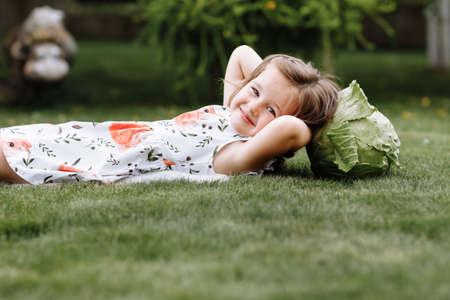 A cute little girl is playing with her pet dog outdooors on grass at home.