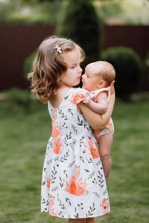 Little cute girl is holding a newborn sister in her arms and spending happy time with her outdoors.