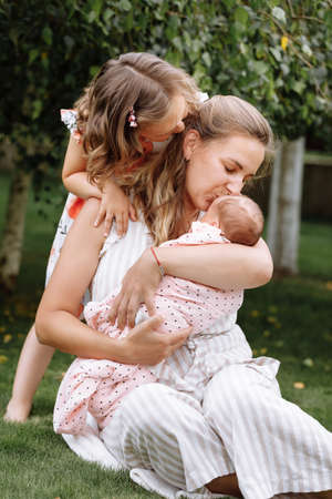 portrait of loving mother and two adorable kids. little girl and newborn baby girl with mom outdoors on summer day. Happy family spent time together in the park.