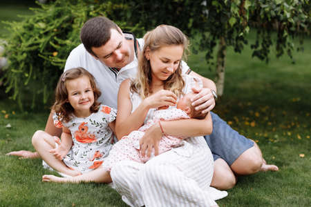 father, mother and two children, baby girl and little daughter on the grass with cabbages on summer day. Happy family sitting together outdoors, having fun. Happiness and harmony in family life