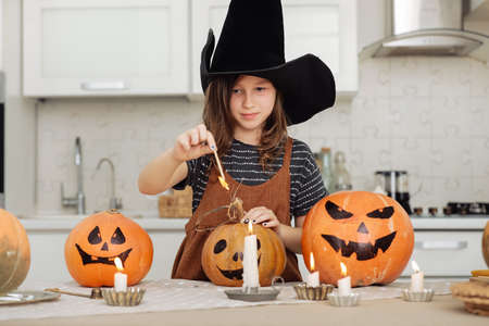 Happy halloween. Cute little girl in witch costume with carving pumpkin. Happy family preparing for Halloween. girl lights candles.