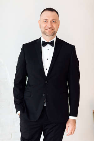 Portrait of a young business man in black suit and bow tie smiling at the camera while holding one hand in his pocket on white background. selective focus