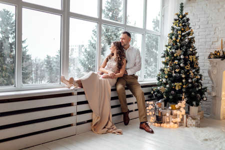 A guy with a girl is celebrating Christmas. A loving couple enjoy each other on New Year's Eve
