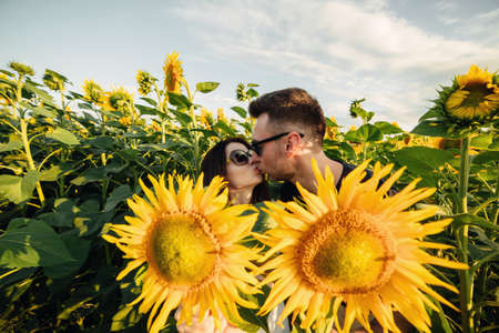 Beautiful couple having fun in sunflowers field. A man and a woman in love walk in a field with sunflowers, a man hugs a woman. selective focus.