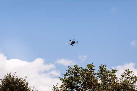 Quadcopter drone in sky. Small drone flies in sky over the park taking video and photos. Remote control air delivery and spy. selective focus Stock fotó