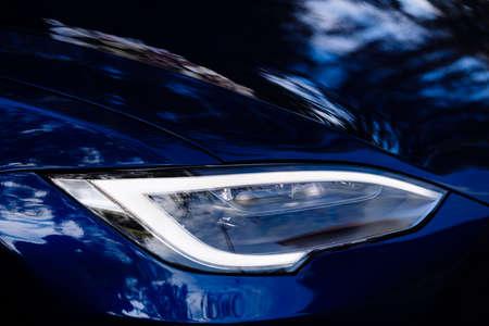 Closeup of new projector headlight on the modern blue car.