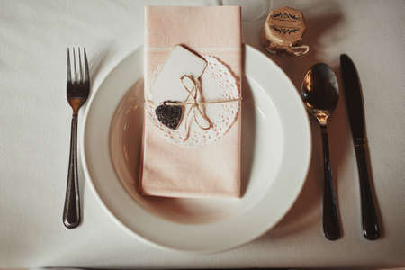 Festive table setting for Valentines Day with fork, knife and hearts