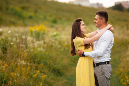 Photo of joyful couple man and woman walking through golden field with bunch of haystacks and hugging together during sunny day.