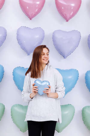 The woman holds the blue balloon in the form of a heart on many hearts background. valentines day. selective focus.