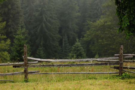 autumn meadow with a old wooden fence on a farm close up, in the Smoky Mountains on a foggy day. travel destination scenic, carpathian mountains.