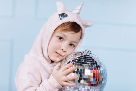 Smiling beautiful little girl in unicorn pink costume is smiling and having fun with disco ball on a blue wall background. happy childhood