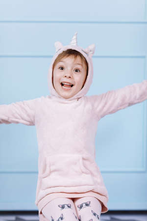 Smiling beautiful little girl in unicorn pink costume is smiling and having fun on a blue wall background. happy childhood
