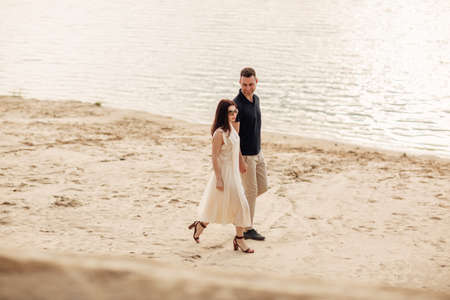 elegant and stylish woman and man in love are walking along the lake. Happy moments together. love story.