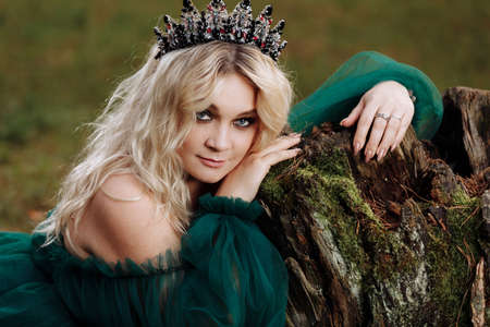 young beautiful blonde hair woman queen. Princess walks. autumn green forest mystic. Vintage medieval shiny crown. Long evening green dress. magic fantasy.