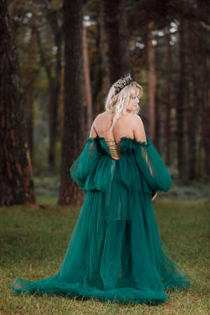 A beautiful blonde young woman in a long green dress and a diadem on her head in the forest. girl sitting near the old stump with amanitas. Solar glare. Fantasy. fairy tale.