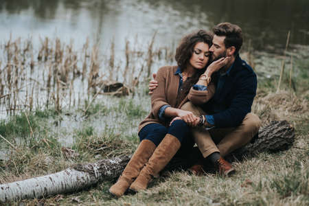 two caucasian lovers sitting on the pier by the lake. Young couple is hugging on autumn day outdoors. A bearded man and curly woman in love. Valentine's Day. Concept of love and family