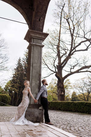 Gorgeous wedding couple hugging and walking near old castle in sunny beautiful park. Stylish beautiful bride and groom posing on background of ancient columns and nature. 스톡 콘텐츠