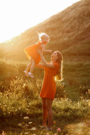 mothers day. womens day. Portrait of smiling beautiful young woman and her little daughter sitting on grass, against green of summer field on sunset