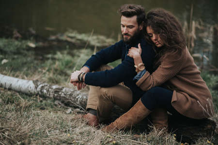 Happy caucasian lovers are sitting on the shore of the lake. Young couple is hugging on autumn day outdoors. A bearded man and curly woman in love. Valentine's Day. Concept of love and family