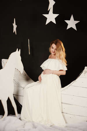 pregnant woman in long white dress touching her belly in decoration studio with stars, moon. Motherhood, pregnant, people and expectation concept. Pregnant woman expecting baby. Maternity concept.