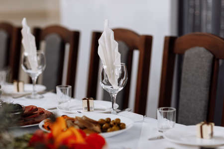 festive table setting with plates, empty glasses and napkins for weddings, birthdays, Christmas and more. restaurant interior.