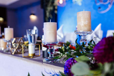 Table setting at wedding reception. Floral compositions with beautiful flowers and greenery, candles on decorated table. Coziness and style. Modern event design. selective focus