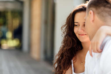 Smiling couple having fun in the park. Love and tenderness, dating, romance, lovers enjoy each other in the summer park. man carry on his back the beautiful curly hair woman smiling and laughing