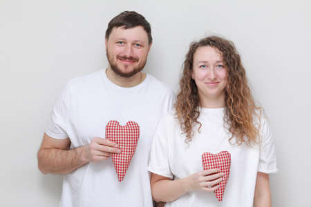 smiling man and woman in white t-shirts with red hearts in their hands lovingly looking at each other. couple in love on a white background