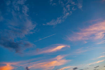 blue sky with clouds and a plane high in the air flies to its destination in broad on sunset or sunrise and leaves a white stripe behind.