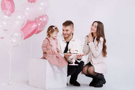 young parents mom and dad are celebrating birthday their two years old child. family light and blowing out the candles on the cake with flowers on the background of birthday decor with pink balls