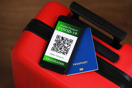 a passport and a smart phone with a certificate of vaccination against the Covid-19 disease. focus on the smart phone. Health Passport concept. travel the world
