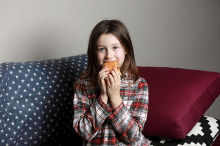 a cute little girl emotionally eating a hamburger, sandwich, cheeseburger or burger and smiling at home