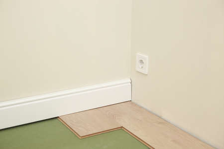 Installing wooden laminate or parquet floor in room over green base. assembling panels quickly and easily - affordable flooring. laying laminate flooring at home.