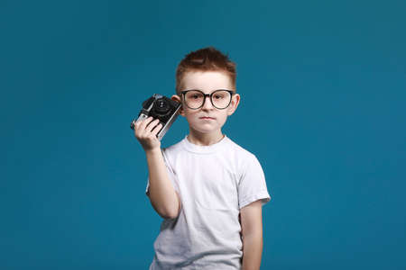 schoolboy in glasses using laptop sitting on bed. Child doing school homework and seriously and tired looking on camera.Online learning, distance lesson, education with online tutor at home isolation. Banco de Imagens