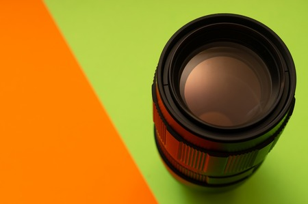 Photo lens on green and orange background with glow on surface