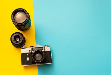 Film SLR photo camera with spare lenses on blue and yellow background