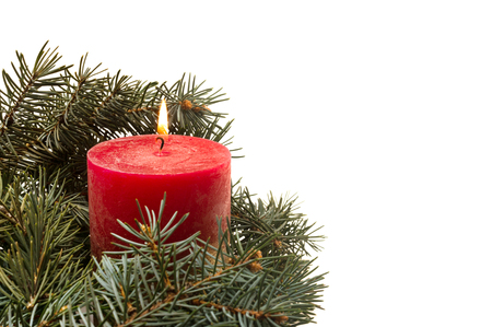White background with and Christmas tree branches and burning candle in the bottom left corner Banque d'images