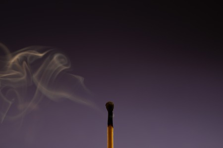 Single burned down match on the violet background