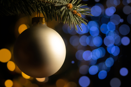 Xmas tree branch with pearl ball on the blurred light blue and golden spots shiny background