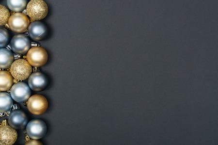 Plusieurs boules de Noël en argent et en or regroupées sur le côté gauche du fond noir
