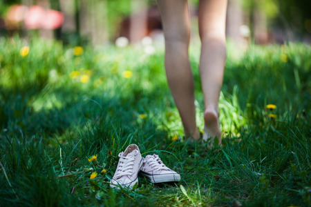 Woman walking barefoot on the green grass, shoes in focus, shallow DOF Foto de archivo