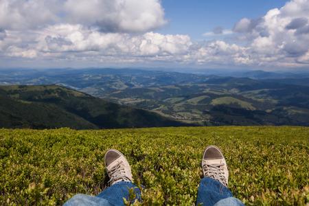 El hombre se sienta en una alta cima de la montaña con la primera persona vista en perspectiva, con las piernas en foco Foto de archivo