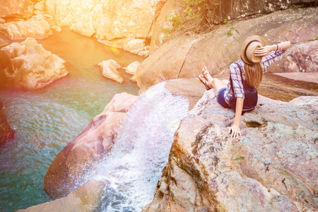 life change: Happy woman sitting on the rock edge near waterfall enjoying stunning view, filtered with sun flares