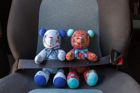 buckled: Stuffed toys buckled with safety belt in a car